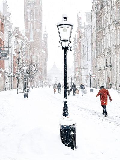 People walking on snow covered street against buildings in city