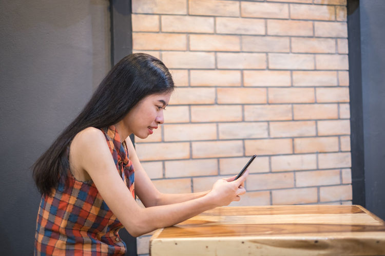 asian women sitting follow social news online with smartphone. he smile happily. Phone Mobile Woman Cell Asian  Females Telephone Young Girl Reading Shop Coffee Using Beautiful Use Sitting Smartphone Lifestyles People Business Leisure Technology person Text Communication Holding Banking News Texting Restaurant Hipster Modern Caucasian Travel Portrait Internet Fashion Indoor Smart Home Youth Watching Website Women One Person Real People Young Adult Young Women Wireless Technology Indoors
