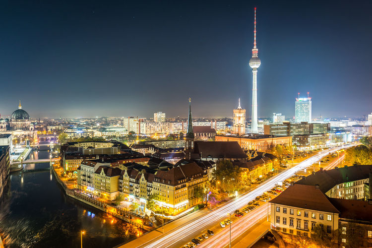 Illuminated fernsehturm and cityscape against sky at night