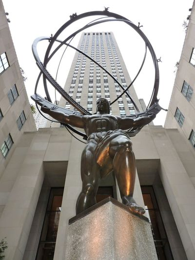 Low angle view of sculpture on street against building