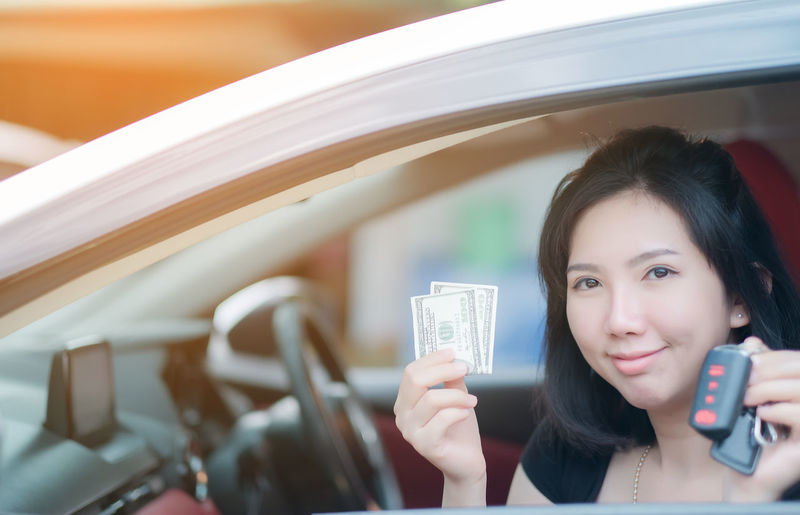 Closeup portrait happy smiling attractive asia woman sitting in her new white car showing keys, holding dollar Personal transportation purchase concept Holding Young Women Portrait Young Adult One Person Headshot Lifestyles Women Smiling Front View Adult Happiness Focus On Foreground Leisure Activity Looking At Camera Real People Emotion Beautiful Woman Outdoors