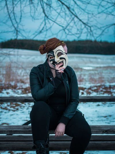 Woman Holding Mask Over Face While Sitting On Bench