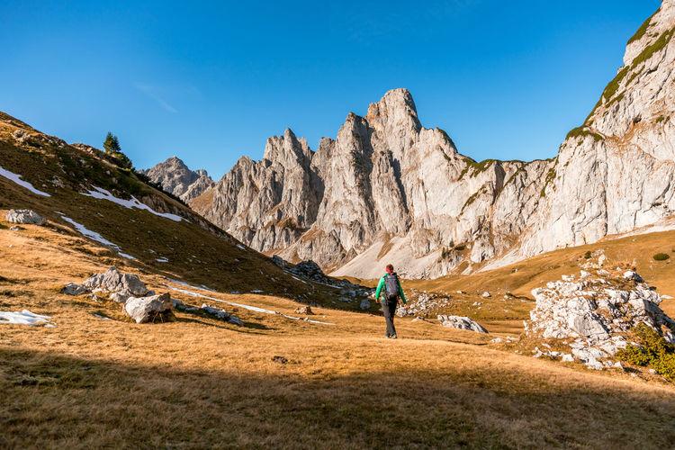 Woman hiking on footpath in alpine landscape in autumn, bischofsmütze, filzmoos, austria