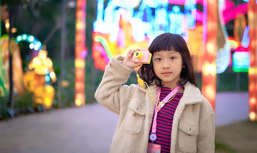 Portrait of cute girl standing in illuminated carnival