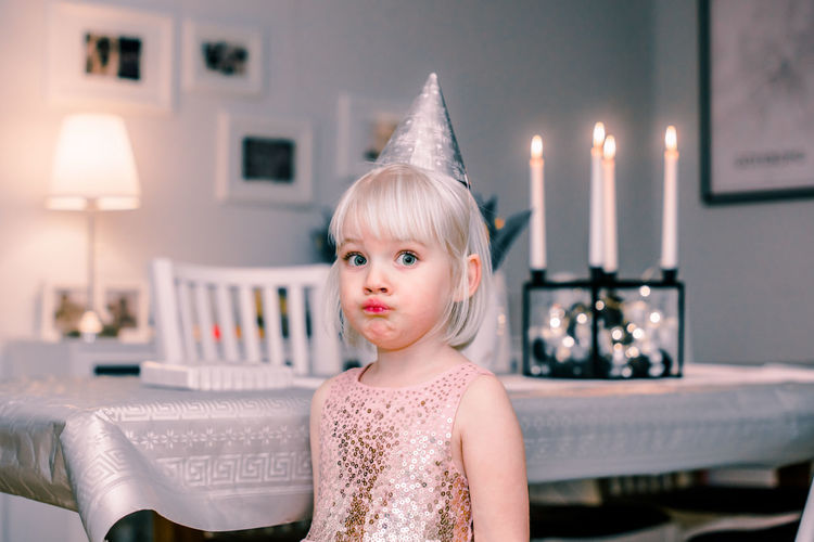 Portrait of girl wearing party hat making face while standing at home