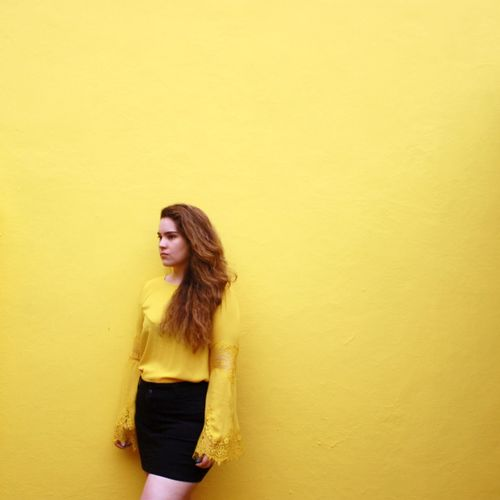 Young woman looking away while standing against yellow wall