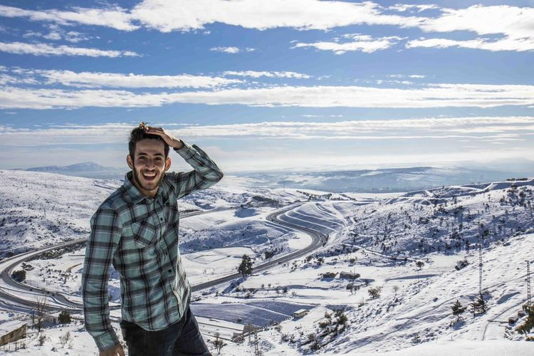 Portrait Of Smiling Man Standing On Snow Covered Landscape