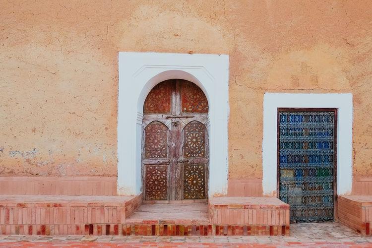 Old moroccan door against orange pink wall in marrakesh