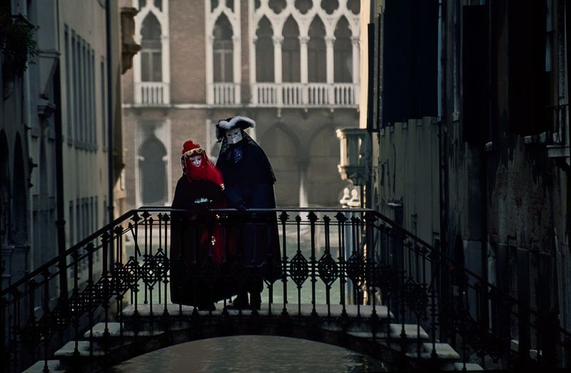 Couple in costumes on bridge over canal in venice