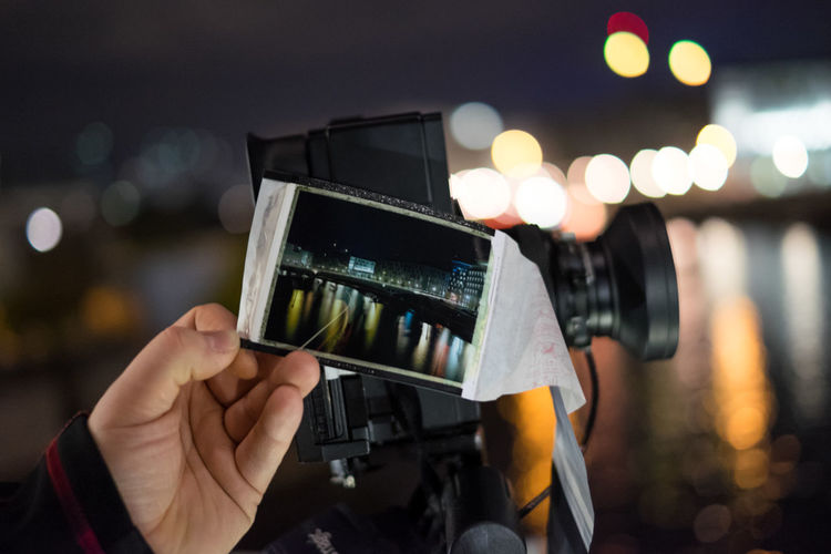 Cropped Image Of Person Holding Instant Print Transfer By Camera At Night