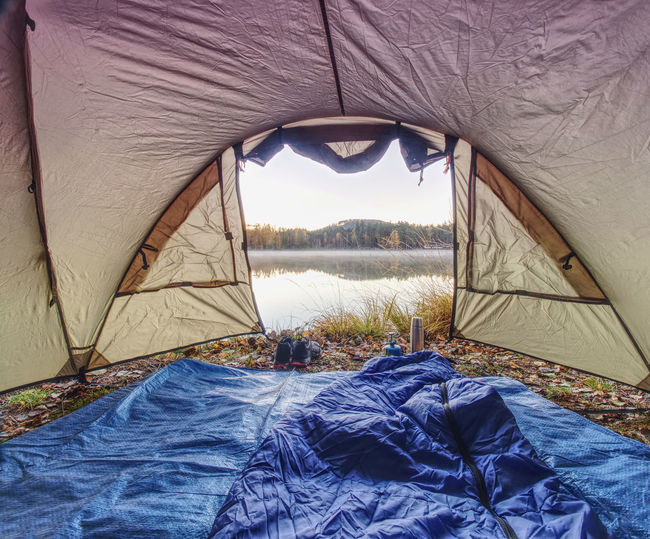 Scenic view of tent on shore against sky