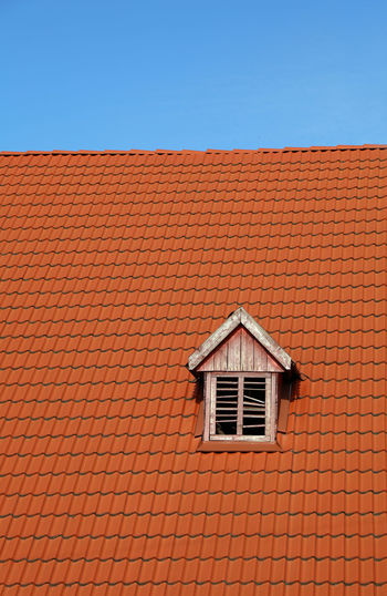 Red, vivid orange ceramic tile roof with garret window under clear blue sky Architecture Blue Blue Sky Brick Building Building Exterior Built Structure Clear Sky Day Garret House Houses And Windows Low Angle View No People Orange Outdoors Red Lips Roof Roof Tile Tail Tiled Roof  Window The Graphic City