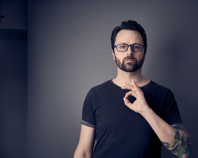 Portrait of man gesturing ok sign while standing against wall