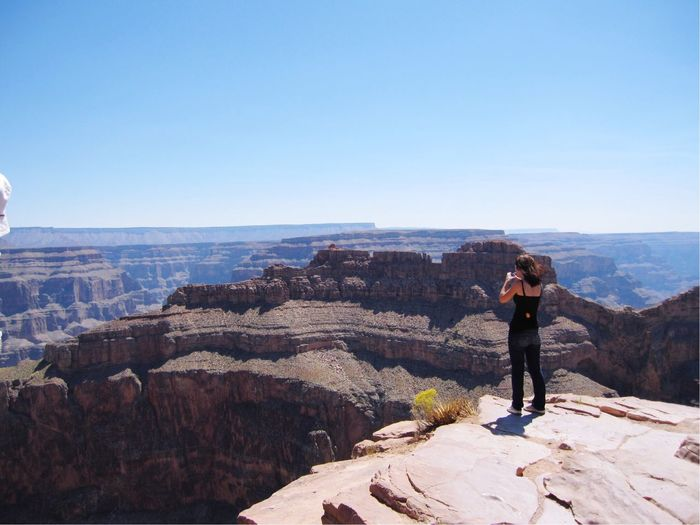 Rear View Of Woman Photographing While Standing At Grand Canyon On Against Sky During Sunny Day