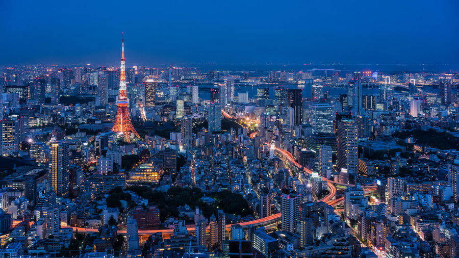 Aerial view of illuminated tokyo tower amidst buildings in city at night