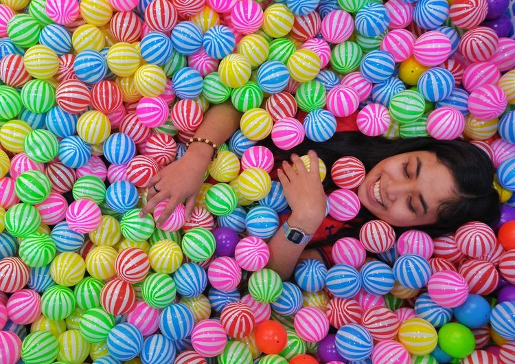 Directly Above Shot Of Woman Lying In Ball Pool