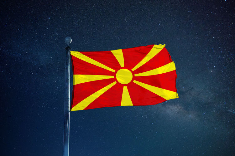 Low Angle View Of Macedonian Flag Against Star Field Sky