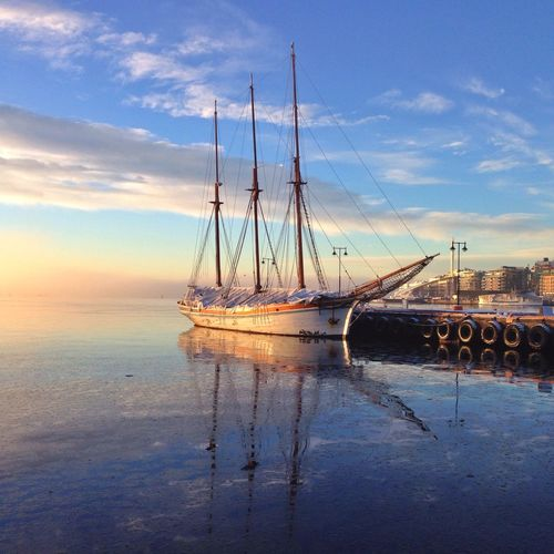 Boat moored at harbor against sky during sunset