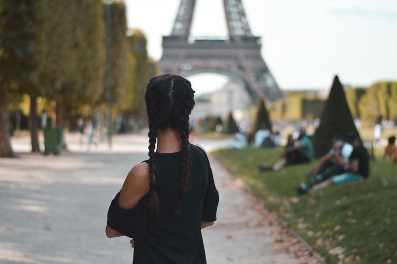Rear view of woman standing on road against eiffel tower in city
