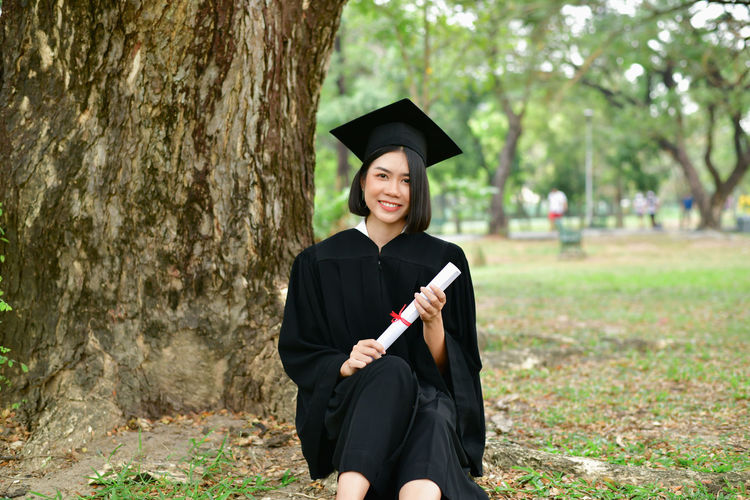Beautiful Happiness Achievement Beautiful Woman Day Education Educational Focus On Foreground Graduation Graduation Gown Holding Land Mortarboard Nature One Person Outdoors Plant Portrait Real People Student Studying Success Successful Tree Young Adult