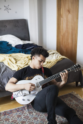 Young man playing guitar on bed