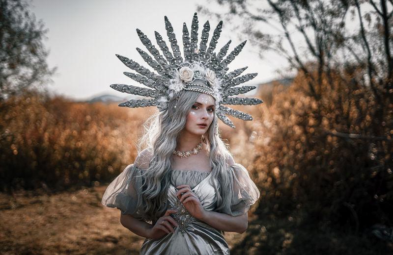 Portrait of woman wearing costume standing on field