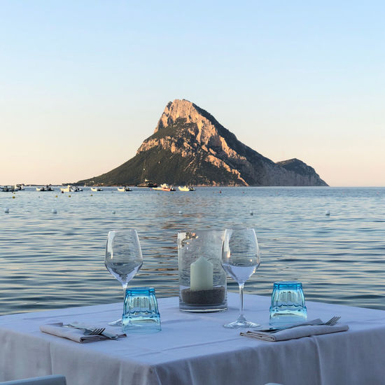 Lounge chairs and table at beach against clear sky dinner wine sunset