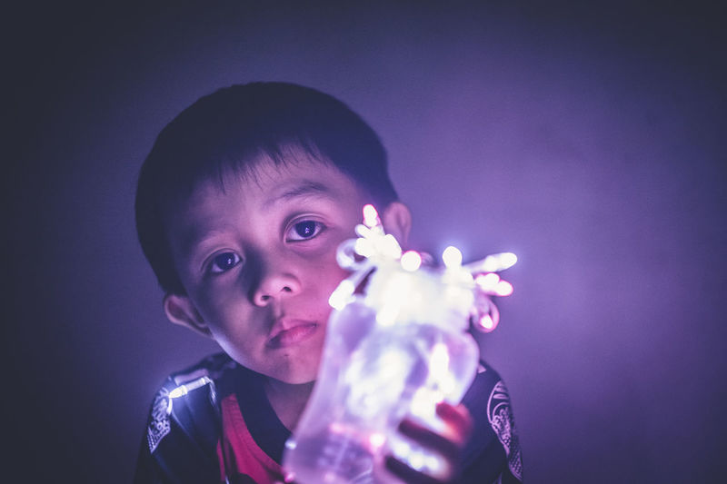 Close-Up Of Boy With Fairy Lights