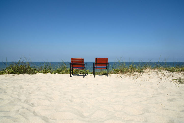 Chairs on sand against sea