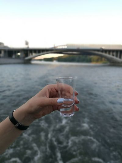 Cropped hand of woman holding drink against river