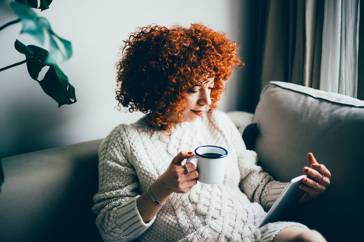 Young woman holding coffee while sitting on sofa at home