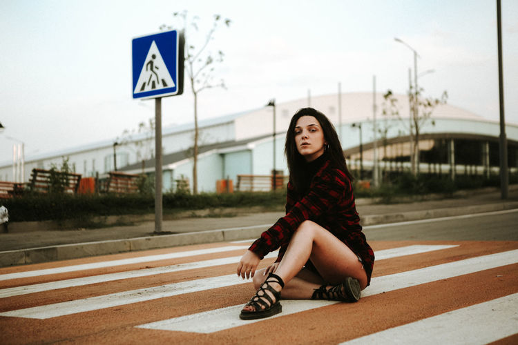 Architecture Beautiful Woman Casual Clothing Day Front View Full Length Hair Hairstyle Long Hair Looking At Camera Nature One Person Outdoors Road Sign Sitting Sky Teenager Transportation Young Adult Young Women