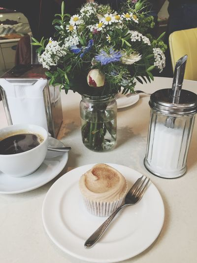 High Angle View Of Cupcakes And Coffee By Flower Vase On Table