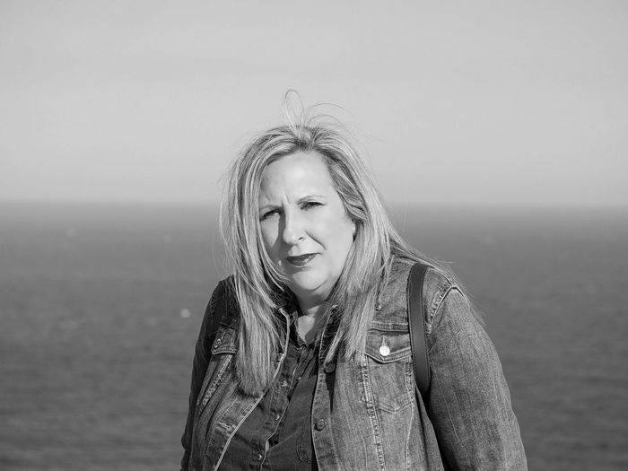 Portrait of woman standing against sea