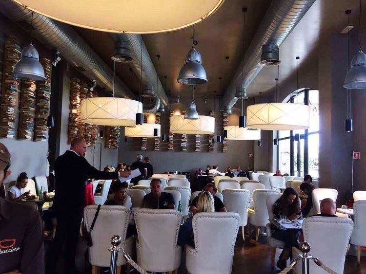 Large Group Of People Indoors  Restaurant Restaurant Scene Sitting People Adults Only Adult Lamps Chairs Armchairs Maitre Eating Lunchtime Day Books Books On The Wall Wall Decoration