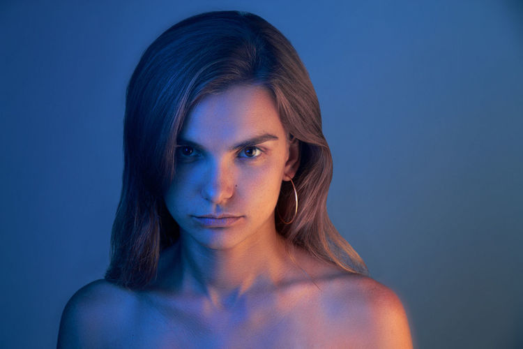 Portrait of young woman against blue background