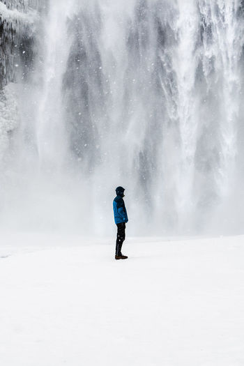 Side view of man standing on snow covered field against waterfall
