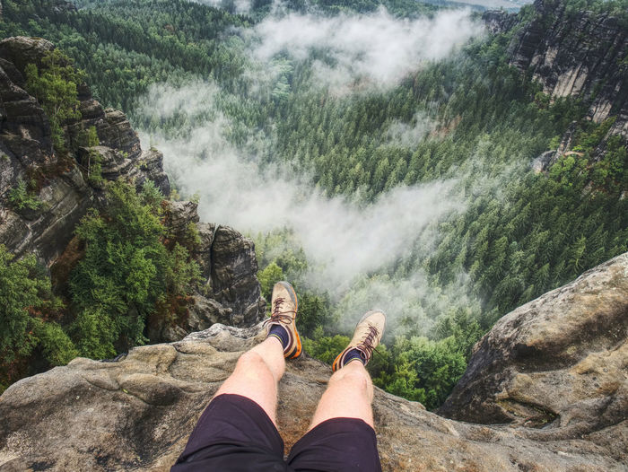 Hiker man take a rest on mountain peak. male legs on sharp summit and hiker enjoy spectacular view.