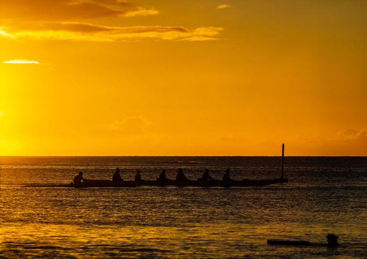 Silhouette boats in sea against orange sky