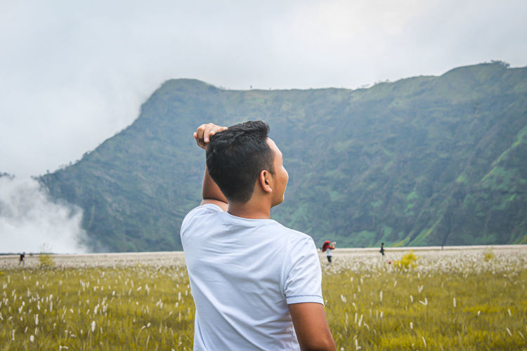 Young man looking at mountains against sky