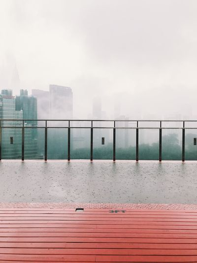 View of swimming pool by railing against cityscape