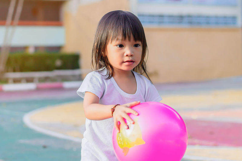 Cute girl playing with ball at park