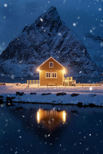 Illuminated house by lake against snowcapped mountain