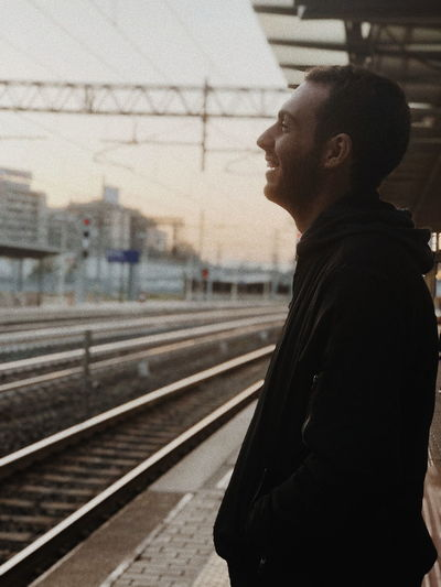 Side view of man standing at railroad station