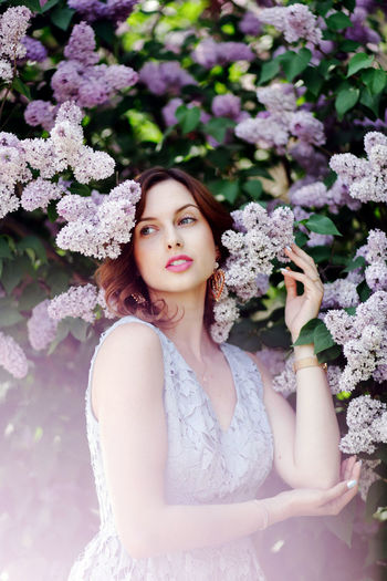 Adult Beautiful Woman Beauty Flower Flowering Plant Hair Hairstyle Leisure Activity Lifestyles Lilac Looking At Camera Nature One Person Outdoors Plant Portrait Real People Standing Women Young Adult Young Women