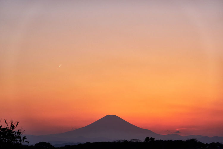 Scenic view of silhouette volcanic mountains against orange sky