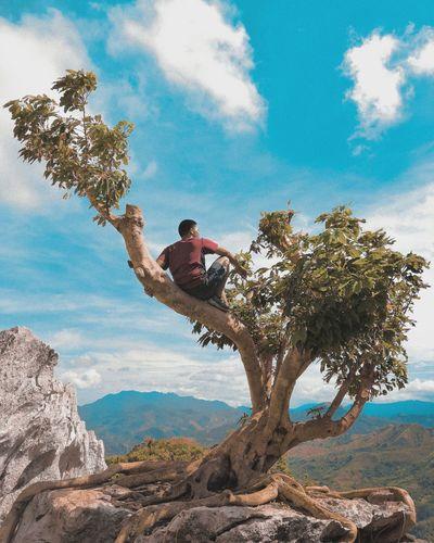 Man sitting on rock against sky