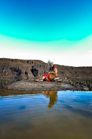 People sitting on rock against blue sky