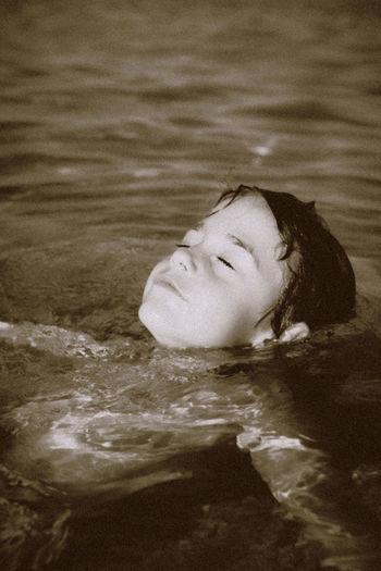 Portrait of woman lying in swimming pool
