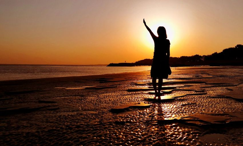 Silhouette woman with arms raised standing on beach against sky during sunset